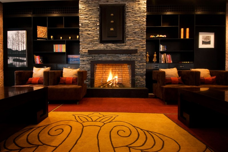 Black-bookcase-Floral-pattern-carpet-Cozy-fireplace-Rustic-brick-wall