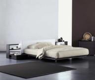 Black carpet Low profile bed Black bedside table White table lamp