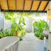 Block paved path Fresh greenery White porcelain bath tub Gloomy wall light
