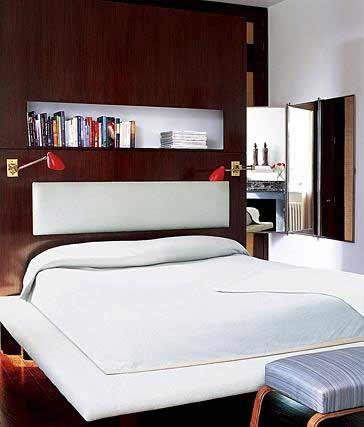Bookcase headboard Low profile bed Padded footstool Modern wall light