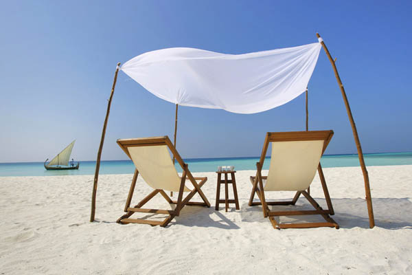Bright white sand Wooden reck chairs Rustic canopy Fascinating beach view