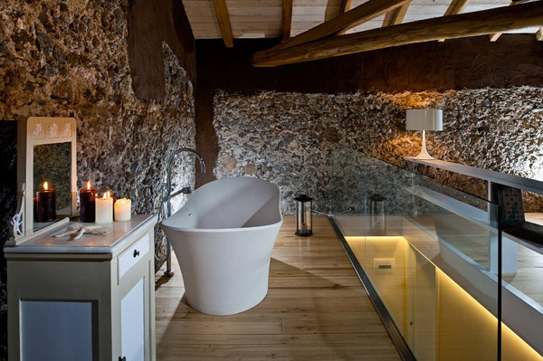 Cozy bath tub Glass railing Natural stone wall Antique dressing table
