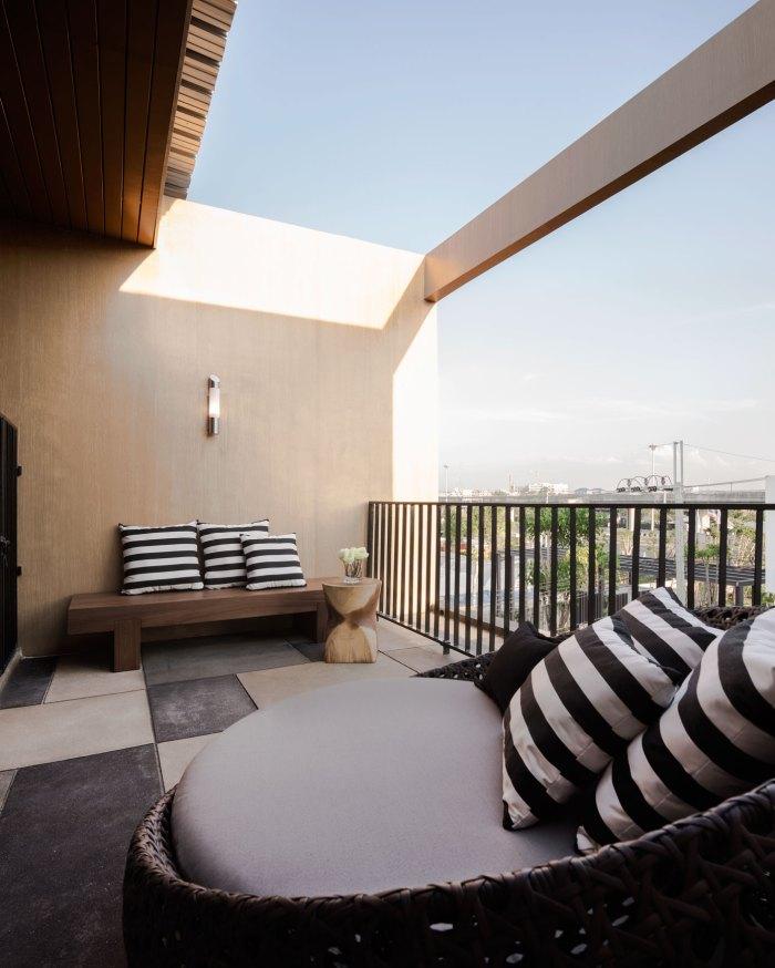 Dark Brown Rattan Sofa Black Striped Cushions Wooden Roof Black Fence