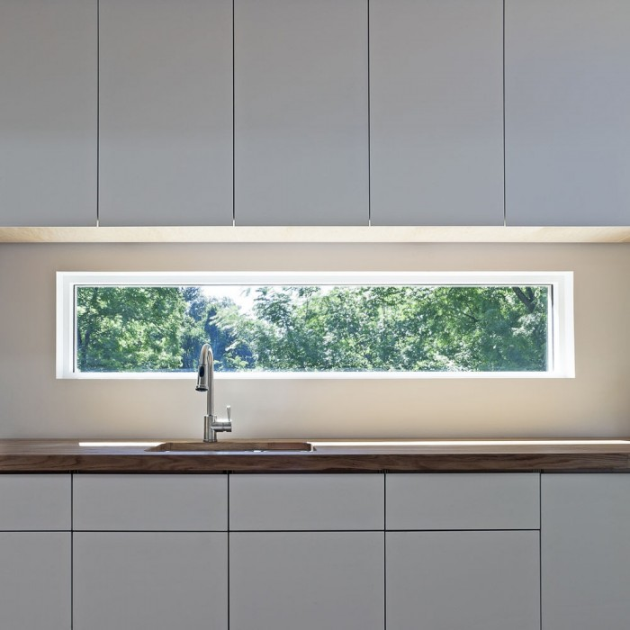 Glass WIndow Backsplash White Counters White Cabinets White Wall