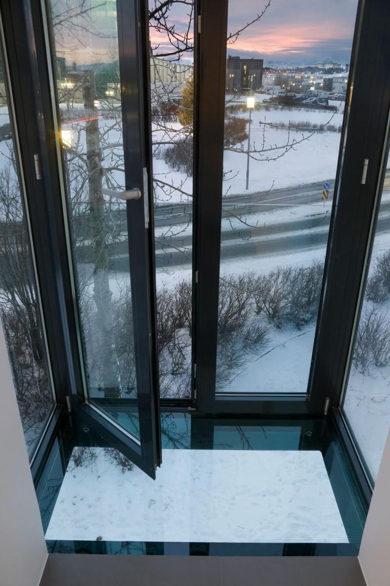 Glass door Shiny marble floor Snowy courtyard Reykjavik apartment