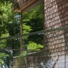 Glass railing Leafy trees Rustic brick wall Twin houses