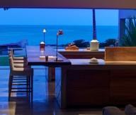 Glossy bar  countertop La punta house Padded barstools Glass wall