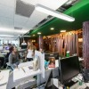 Green Wall Wooden Pillars White Desks Neon Bar Lamps