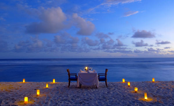 Incredible ocean view Outdoor lights White tablecloth Wooden arm chairs